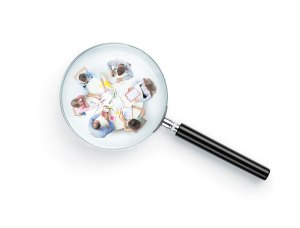 Photo of magnifying glass with business people all inside of the lens