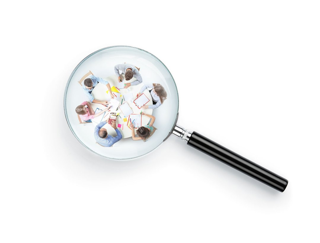 A magnifying glass focused on a team of workers.