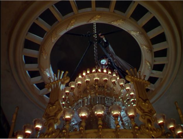 Rains and that damned chandelier. Lowering the lights.