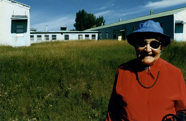 1997, Charlotte Ruth Stone (ret. School Principal) stands by southside of Sagehill School on the entrance road.