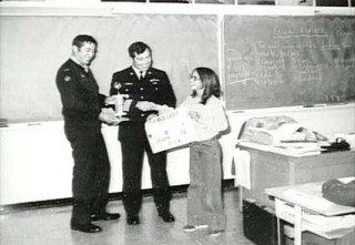 Student receiving an award in class from officers at Sagehill School, CFS, Dana Saskatchewan.