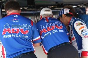 Takuma Sato speaks with his crew members.