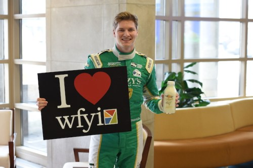 Ed Carpenter Racing driver Josef Newgarden delivers a bottle of milk to the local media (Photo Courtesy of IndyCar - Chris Owens)