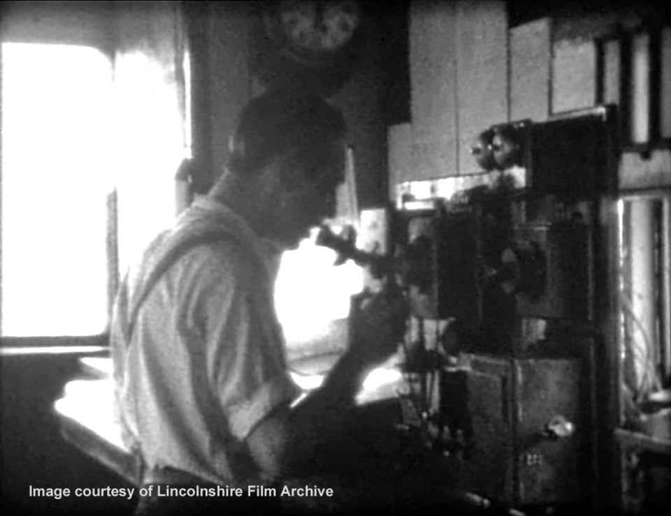 The telegraph lad on the telephone at the south end of the box. Behind him is the train register, where the time of every passing train and of every communication with other signal boxes was recorded. From a film shot by Walter Lee. © Lincolnshire Film Archive