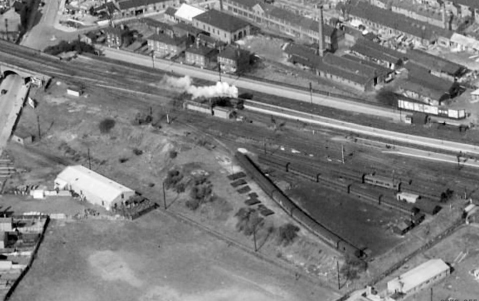 The box and its relay room are seen just above centre in this view taken on 19th April 1950. A locomotive steams past approaching the north end of the station, probably heading for the Yard Box engine siding to wait for a southbound train which it is due to take forward. The sidings at lower right, being used to store old coaches, are part of the Civil Engineer's yard. Photograph from Britain From Above © English Heritage.