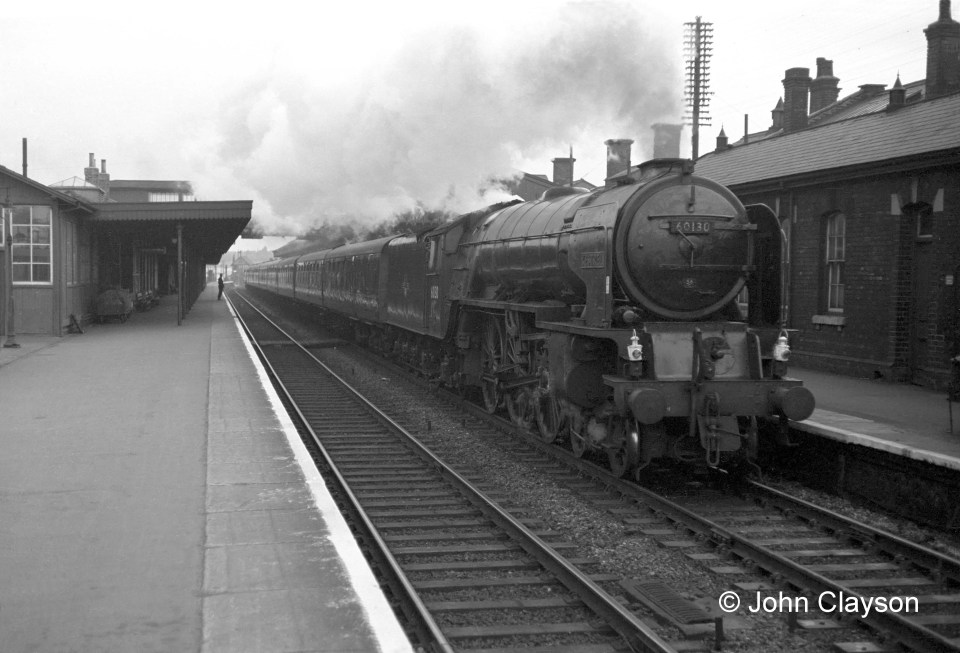 A southbound express passenger train speeds through the station on 25th May 1962, hauled by class A1 locomotive No.60130 Kestrel of Copley Hill shed (56C) in Leeds. This is the point at which Alan's driver would prepare to 'drop the lever', a saying going back to Victorian times when all locomotives had a large vertical lever which worked in a notched quadrant on the driver's side of the cab. The driver would 'drop' the lever down, or forward, by a notch or two to increase power and maintain speed up a gradient. From around the 1900s the lever was replaced by a rotating handle on most locomotives, except those intended for low powered freight and shunting work. This explains why Alan says '...drop the lever down half a turn or more...'. Photograph by Cedric A. Clayson