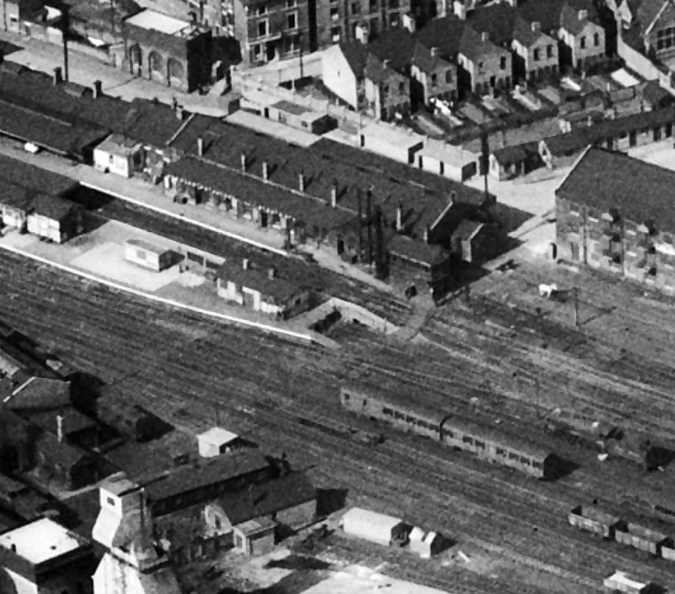 Grantham Yard signal box is at the platform end, slightly to the right of centre in this photograph, which was taken on 19th April 1950. The station platforms and buildings lie to its left, with the station water tower near the top left corner, across Station Road. At lower left are the Loco Department offices and workshops, with the top of the shed water tower and the coaling plant at the bottom left corner. Photograph from Britain From Above © English Heritage.
