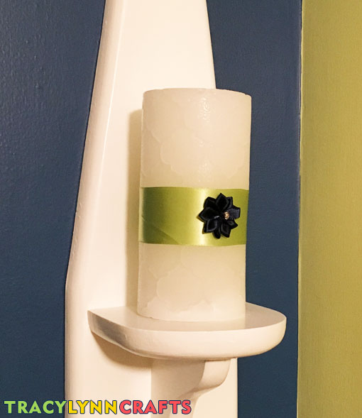 Repainted wall sconce with a decorated LED candle