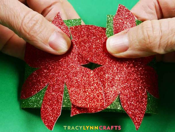 Close the envelope by interlocking the petals of the poinsettia