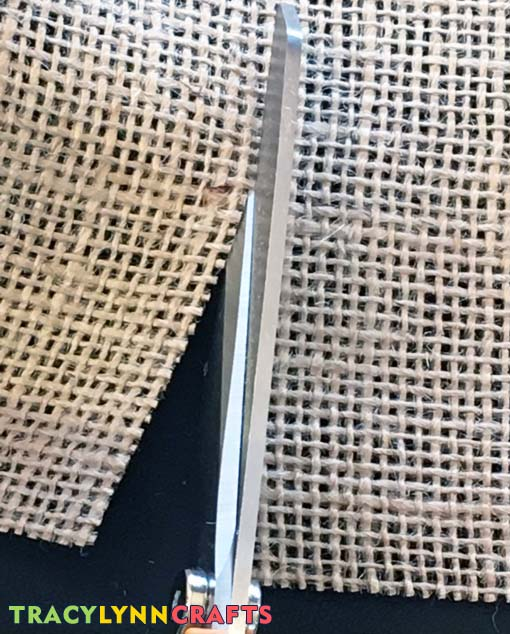 Cut between the fibers of the weave when cutting burlap to reduce fraying