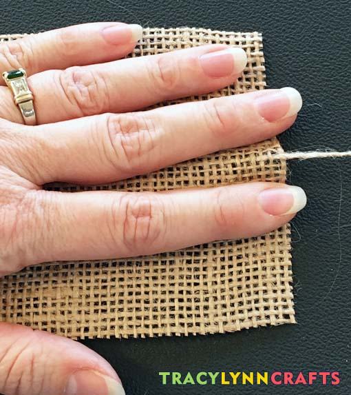 Hold the burlap with your hand and pull the fiber out of the cloth