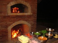 Mto brick oven with fireplace under a hut