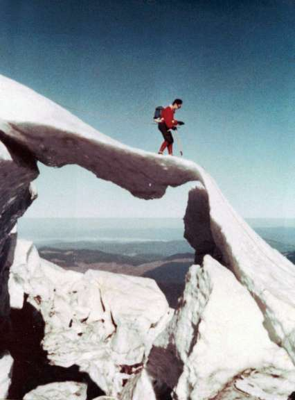 A woman with ice axe in hand descends a sheet of snow that appears suspended in the air.