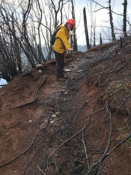 A woman in yellow jacket and orange hard hat bends over a rutted curve of trail on a steep, burned-over slope.