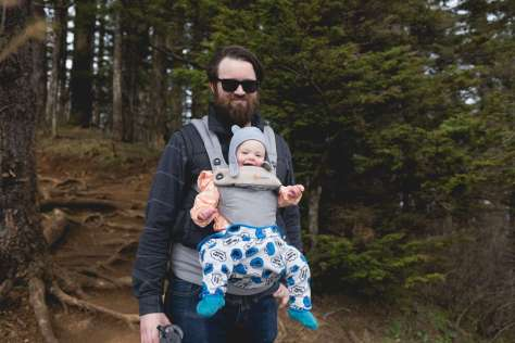 A man with a baby—who seems to be wearing voluminous pants—in a baby carrier on his chest, standing against a backdrop of a coniferous forest,