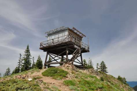 A cabin on stilts sits on a mountaintop with open sky behind.
