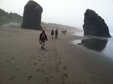 Five people walk along a beach between two large monoliths rising out of the sand.