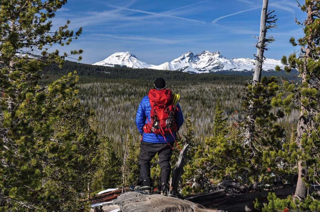 A man with a red backpack stands in the foreground with snowy mountains in the background.