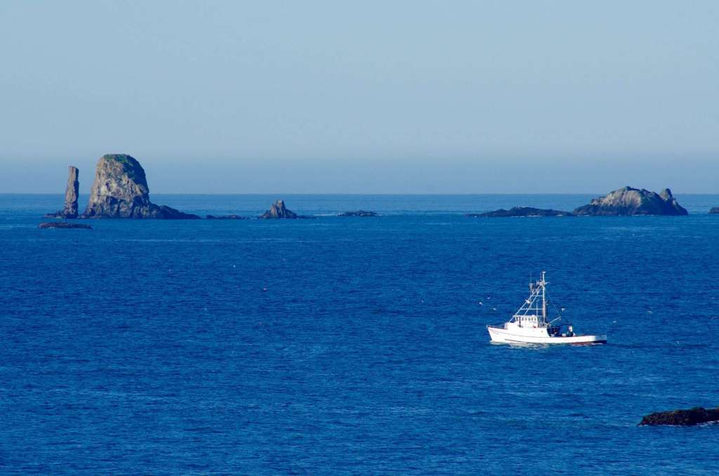 A row of rock islands in a blue ocean with a fishing boat passing in front.