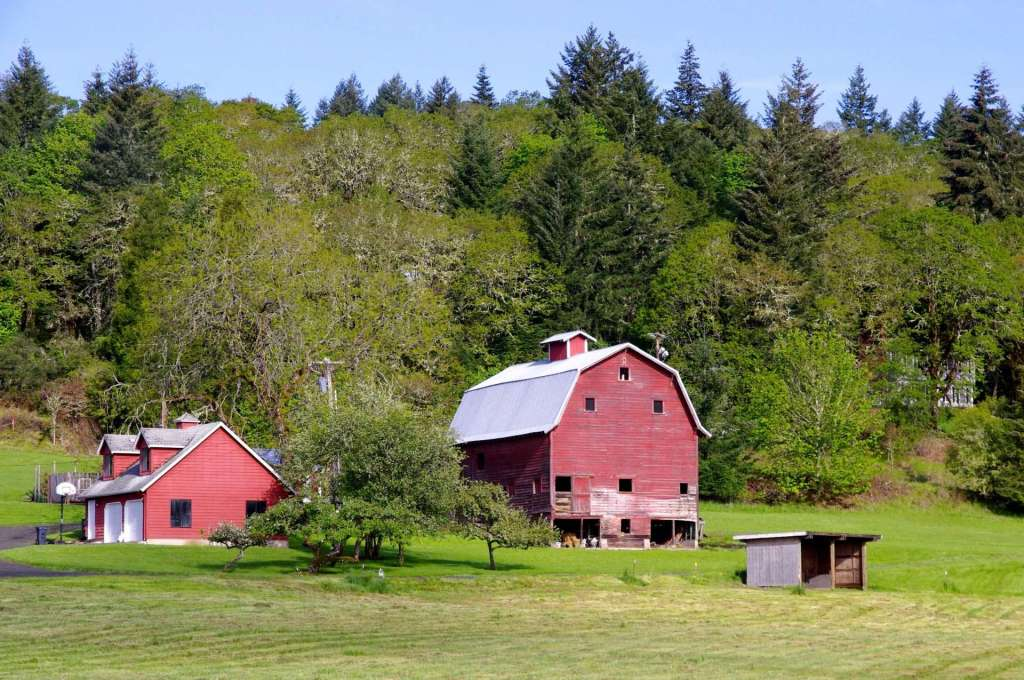 A red house and red barn with a white roof in front of a tree-covered hill.