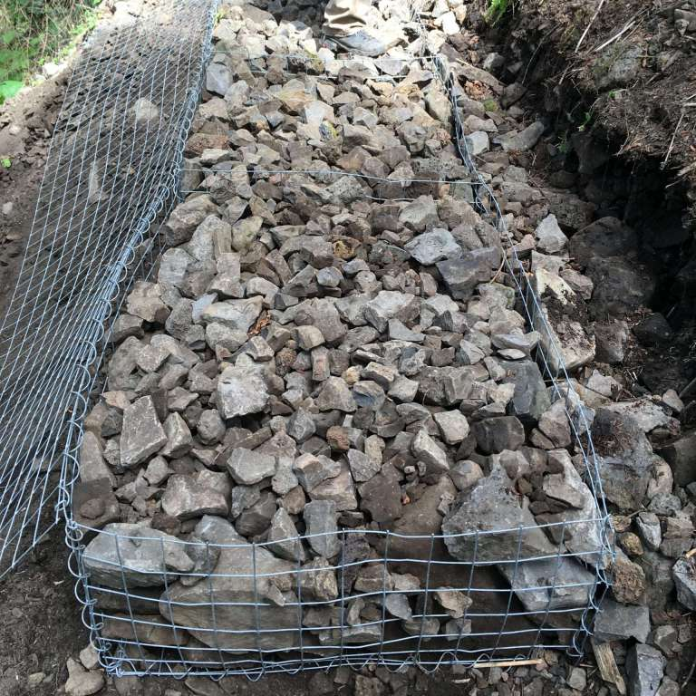 A large wire basket filled with rocks.