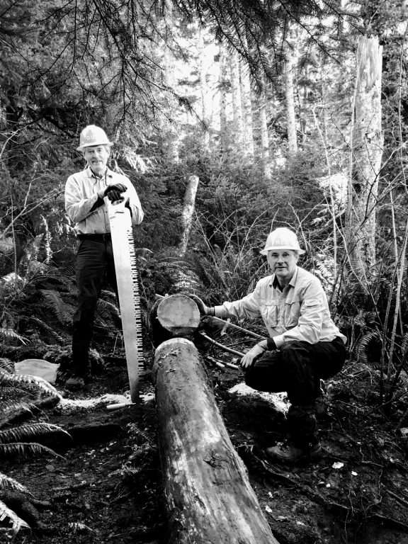 Two men on either side of a cut-through log, one standing with his hands on a long saw, the other kneeling by the cut log.
