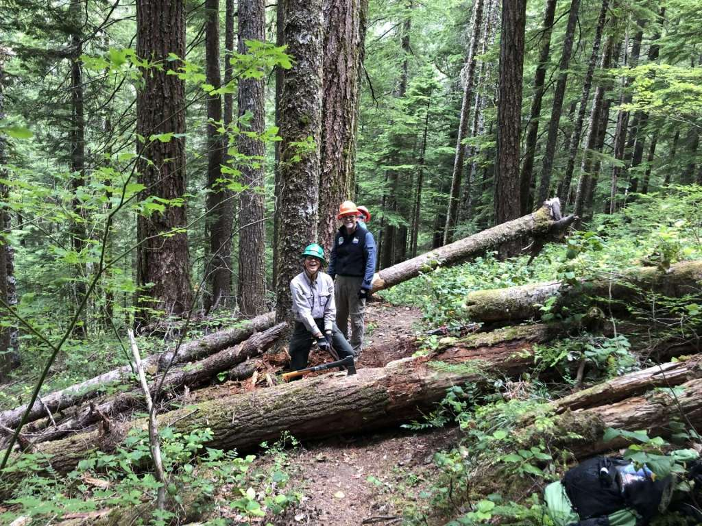 Three workers with a log across a trail in front of them and another across the trail behind them.
