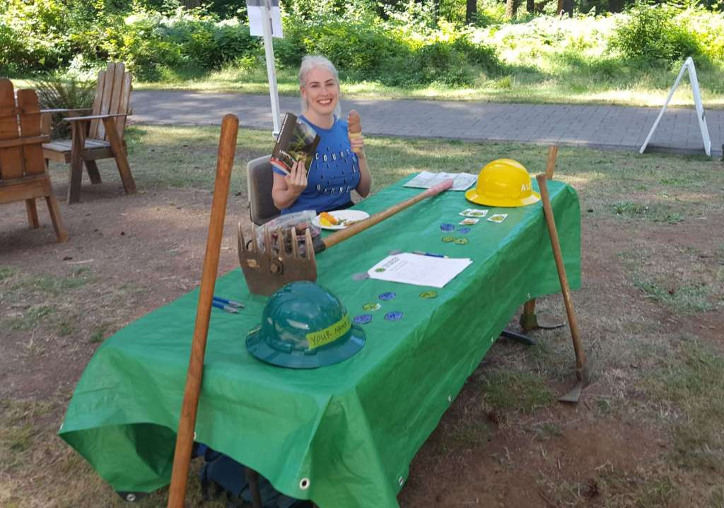 A smiling woman holding a book and an ice cream cone sits outdoors at a table which has hardhats and a McLeod trail tool on it.