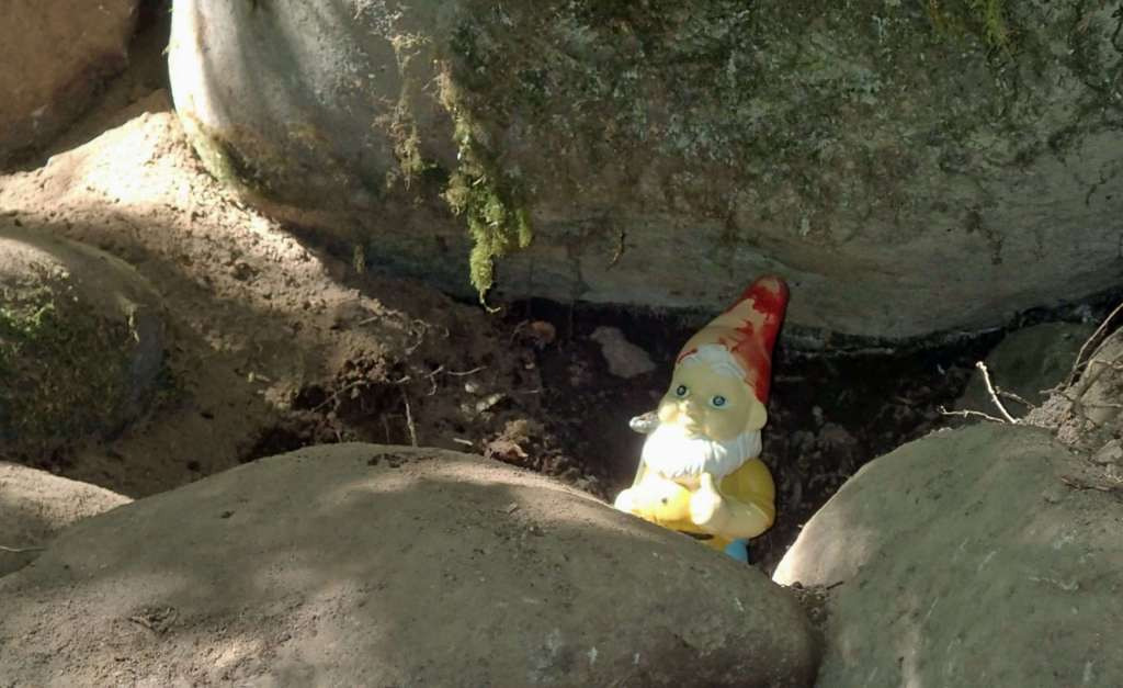 A garden gnome looking out from some boulders.