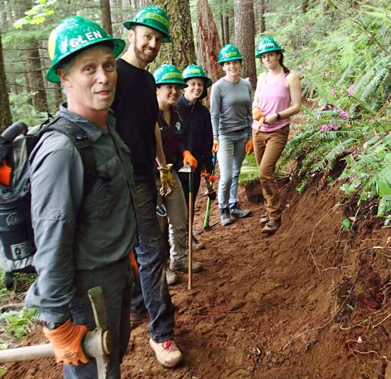 Six trail workers in green hard hats stand on a restored section of trail and smile at the camera.