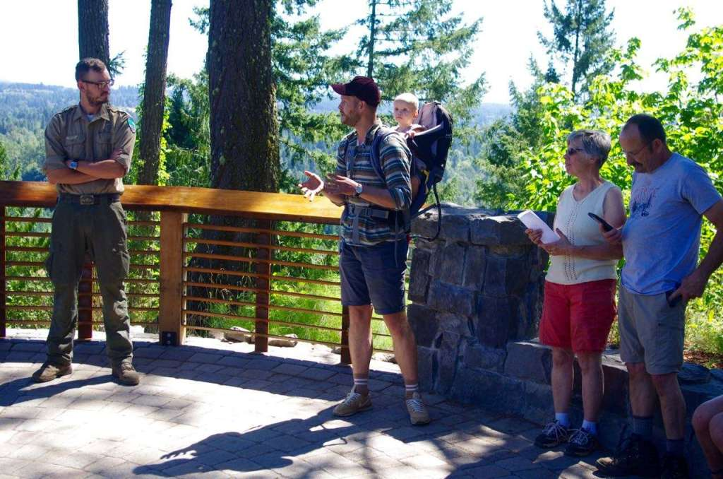 A park ranger in uniform, a bearded, gesturing man with a baby on his back, and another man and a woman stand with backs to a guard rail.