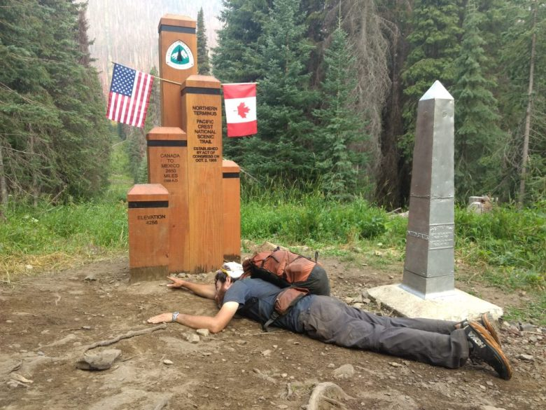 A Pacific Crest Trail thru-hiker struggling to touch the Northern PCT Terminus, marking the completion of the hike.