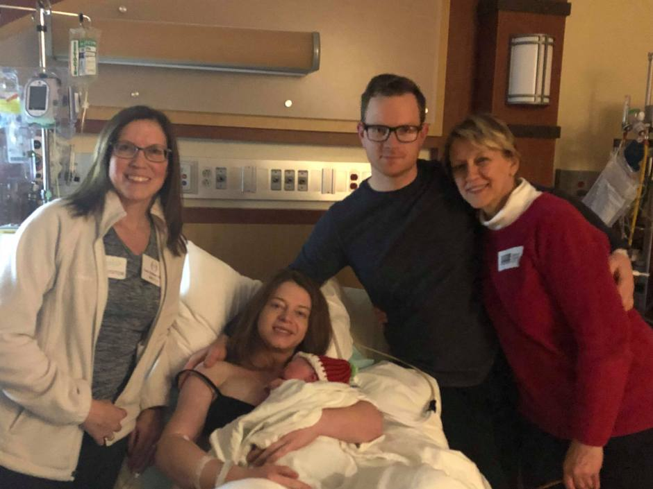 Doula Lora Schnurr standing next to birth family in hospital room