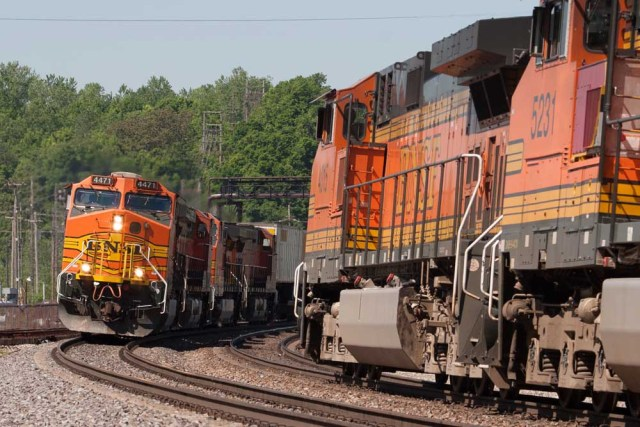 Freight trains with orange diesel locomotives pass on curve
