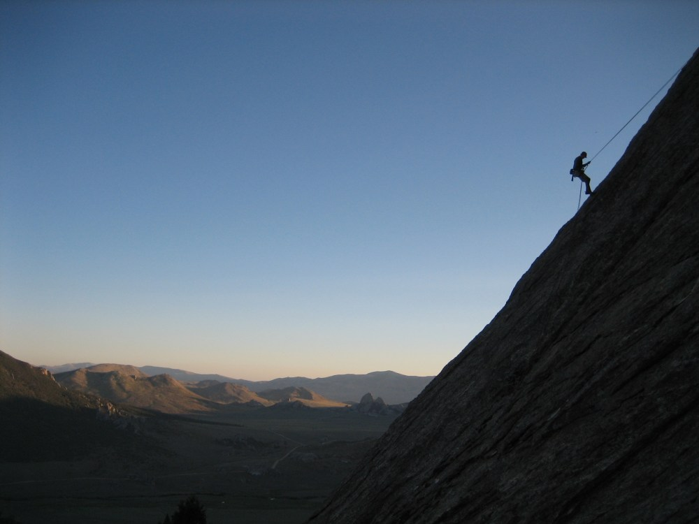 Rappelling off a long climb at sunset in the City of Rocks.