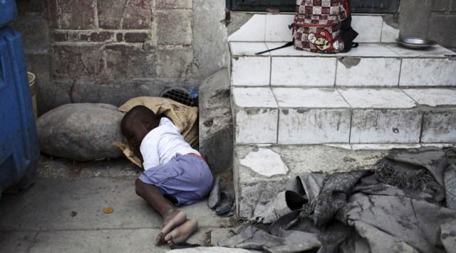 A boy takes a nap on a street in Port-au-Prince, Haiti. © Andres Martinez Casares / Reuters