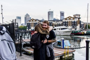 Professional Photography White Man With Beard Wearing Black T-Shirt And Grey Hoody Around Waist Hugging Woman In Limehouse Basin With Boats River Canal And Canary Wharf Buildings In Background