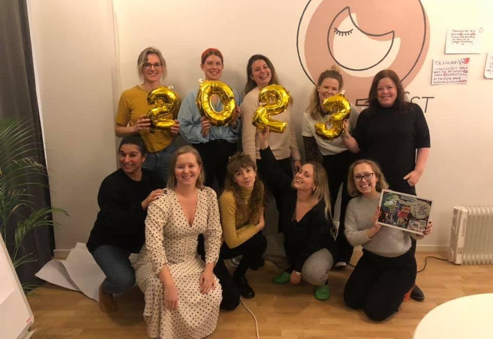 Tio personer har ställt upp sig på två rader och ler mot kameran. Översta raden håller i guldiga siffer-ballonger som läses 2023.