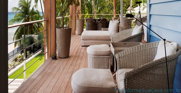 Überdachter Balkon mit bequemen Sitzmöbeln mit Blick auf Palmen und Strand