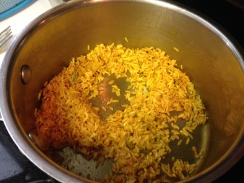 Dark yellow/orange rice, fried in metal pot with some fat and spices.