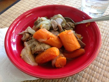 This braised lamb shank homemade recipes in a red bowl, over a bamboo placemat. Spoon in bowl. Contains large soft carrot chunks, garlic, white onions, bay leaf, red radish (not seen).