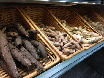 Three fresh roots are shown in whicker bins at grocery store: burdock root, turmeric root, ginger root.