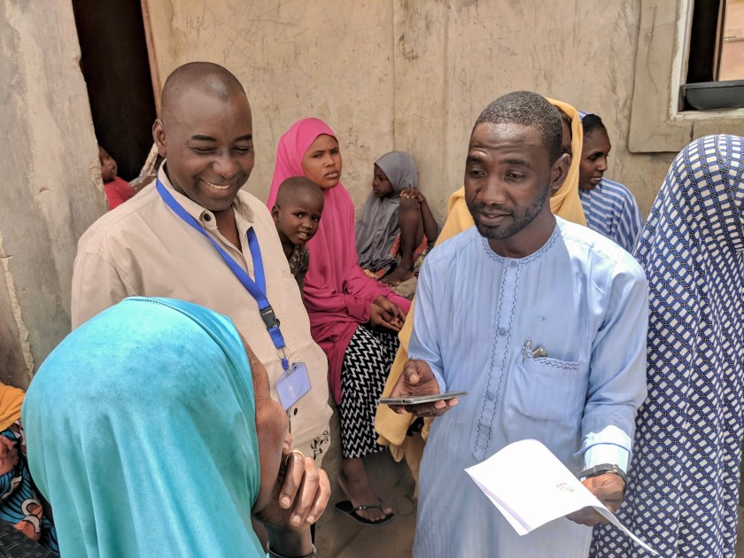 Mustapha (left), TWB - Hausa Team Lead, works with enumerators from the Danish Demining Group / Danish Refugee Council to conduct research on comprehension of information in various languages and formats at Farm Centre IDP Camp in Maiduguri, Borno State, Nigeria.