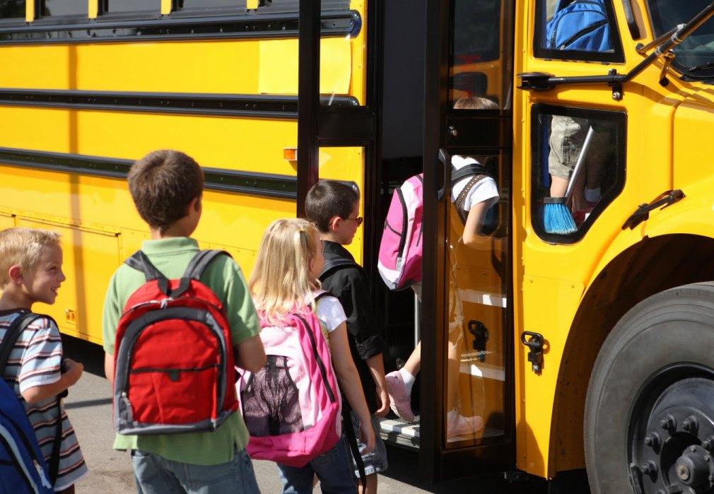 Photo of kids getting aboard school bus