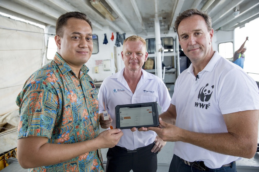 "Ken Katafono, TraSeable Solutions CEO, Brett ""Blu"" Heywood, SeaQuest Fiji CEO and Dermot O'Gorman WWF-Australia CEO showing the blockchain data that records the start of the traceability journey. At the docks, Walu Bay, Suva, Fiji, December 2017. © WWF-Aus / Shiri Ram"