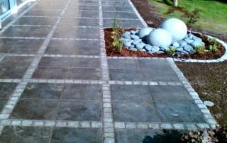 Terrasse aus Kalksteinplatten mit einer Bänderung aus Granitpflaster