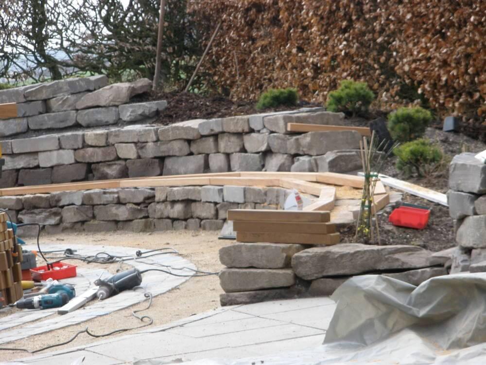 Die Sitzauflagen der Natursteinmauer werden erstellt