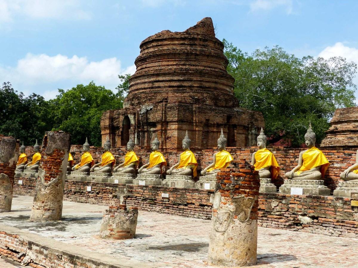 Stone Buddhas in orange dresses in Ayutthaya