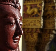 Wooden Buddha head in front of a temple in Chiang Mai
