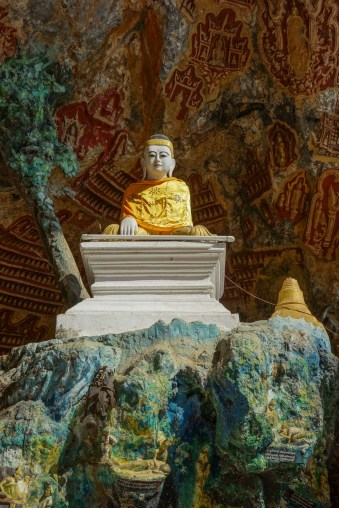 Buddha statue infront of votive tablets decorating the walls of Kawlgoon Cave near Hpa-An